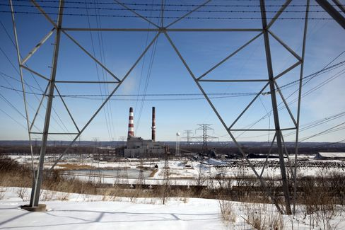 A Power Station Stands Beyond a Transmission Tower