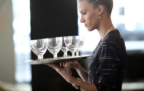 A Waitress Holds a Tray of Glasses