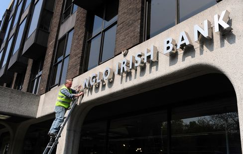 Workmen remove the Anglo Irish Bank Corp. logo from the bank's former headquarters in Dublin. Photographer: Aidan Crawley/Bloomberg