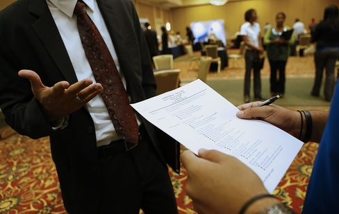 A recruiter, right, reviews a job seeker's resume during a Coast to