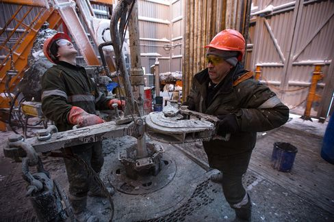 Workers Move Drill Sections On A Shell And Gazprom Venture