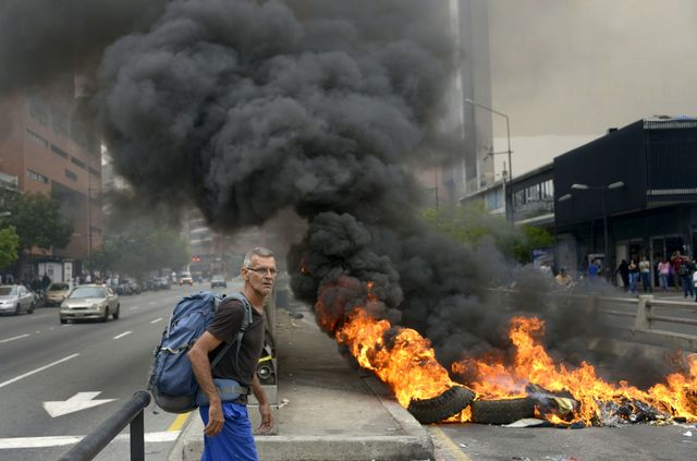 A man passes by a barricade set ablaze blocking a street during a protest against the government of Venezuelan President Nicolas Maduro, in Caracas. Photographer: Raul Arboleda/AFP/Getty Images