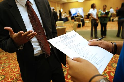 A recruiter reviews a job seeker's resume during a Coast to Coast Career Fairs event in Houston, Texas. Hiring is expected to be limited through the rest of the year. Photographer: Aaron M. Sprecher/Bloomberg