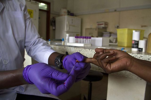 A lab technician draws blood from a patient for HIV testing at the Aids Information Centre in Kampala. Photographer: Isaac Kasamani/AFP/Getty Images