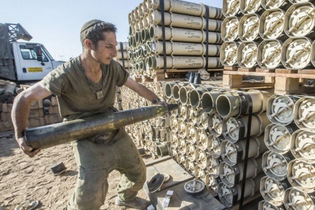 An Israeli soldier carries shells while preparing a tank stationed along the border between Israel and the Gaza Strip.