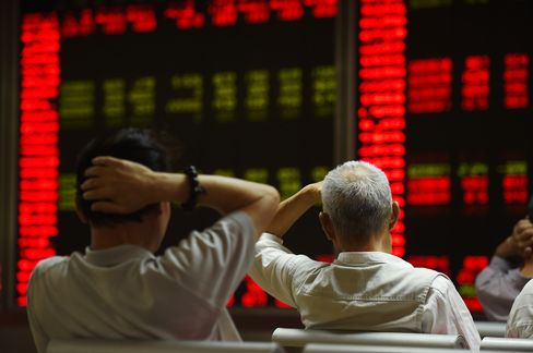Investors react at a securities company in Beijing on July 14, 2015. Photographer: Greg Baker/AFP/Getty Images