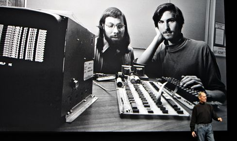 Steve Jobs, co-founder of Apple Inc., right, speaks in front of a file photograph of himself and fellow co-founder Steve Wozniak during the launch of the Apple iPad tablet in San Francisco, California, on Jan. 27, 2010. Photographer: Tony Avelar/Bloomberg