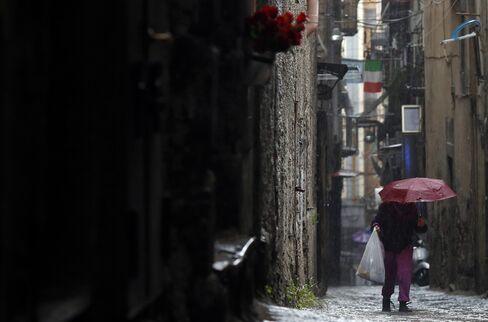 A Pedestrian Walks Along a Street in Naples