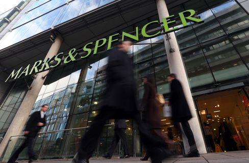 Pedestrians Pass a Marks & Spencer Group Plc Store in London
