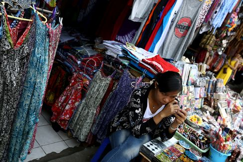 A vendor sits at a stall in the Pasar Ubud market in Ubud, Bali, Indonesia. Indonesia is hampered by inflation close to a four-year high and a record current-account shortfall. Photographer: SeongJoon Cho/Bloomberg