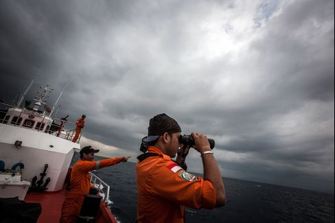Indonesian national search and rescue agency personnel watch over high seas during a search operation for the missing Malaysian Airline System Bhd. jet in the Andaman Sea, on March 15, 2014. Photographer: Chaideer Mahyuddin/AFP via Getty Images