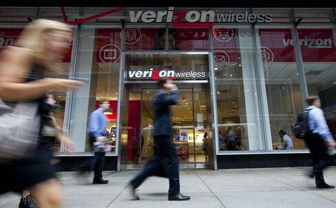 Pedestrians Walk Past a Verizon Store in New York