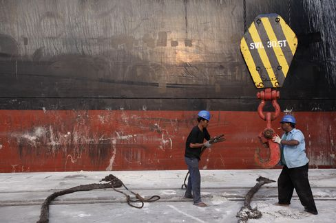 Workers attach ropes onto a crane hook at the Tanjung Priok port in Jakarta. In Jakarta, the capital of Indonesia and home to 10 million people, Governor Joko Widodo last year approved a 44 percent increase in minimum pay for workers, to 2.2 million rupiah ($227) a month. Photographer: Dimas Ardian/Bloomberg
