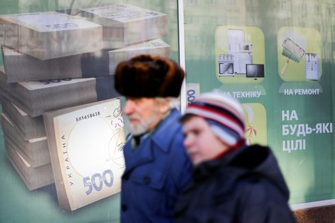 Pedestrians Pass a Bank Advertisement Showing Hryvnia Currency
