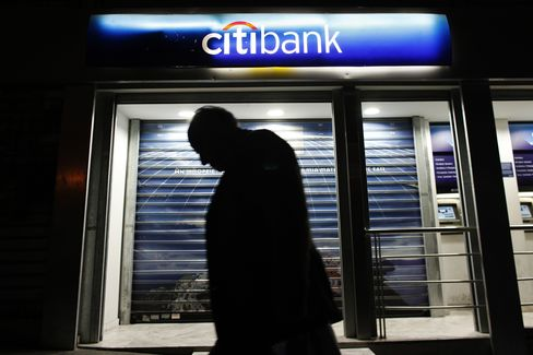 A pedestrian passes an illuminated Citibank branch, operated by Citigroup Inc., in central Athens, Greece, on Thursday, Nov. 22, 2012. Photographer: Kostas Tsironis, Angelos Tzortzinis/Bloomberg