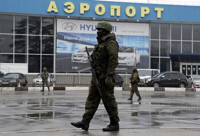 Armed men patrol outside the Simferopol airport in Crimea. Photographer: Viktor Drachev/AFP/Getty Images