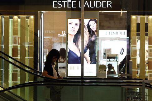 A Woman Rides an Escalator past an Estee Lauder Counter