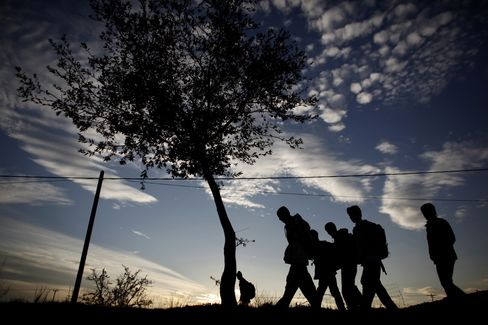 A group of Afghan youths walk along a road in Madamado towards the town of Mytilene after arriving by boat from Turkey in the northern part of the island of Lesbos. Photographer: Kostas Tsironis/Bloomberg