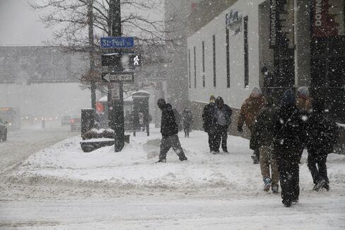 Pedestrians walk along a street during a Snow Storm in Rochester