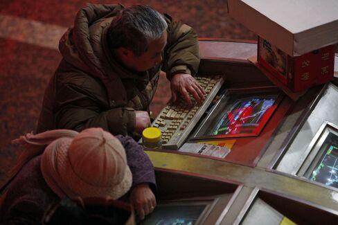Investors Monitor Stock Prices In Shanghai