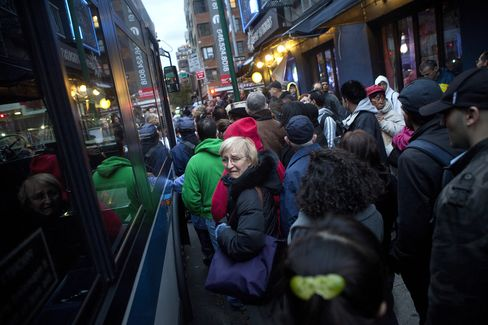 Commuters wait to board a bus headed for the Queens borough in New York on Oct. 31, 2012. Photographer: Victor J. Blue/Bloomberg