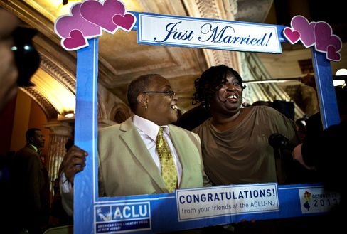A couple poses for a photo after being married by Senator Booker
