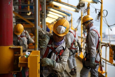 Workers labor at a Total SA Clov floating production, storage and offloading (FPSO) unit under construction in the Daewoo Shipbuilding & Marine Engineering Co. ( DSME) shipyard in Geoje, South Korea, on Tuesday, June 25, 2013.