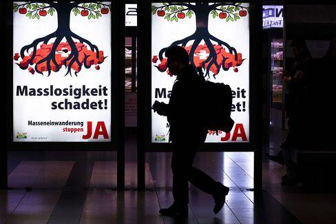 A Pedestrian Walks Past a Poster in Zurich