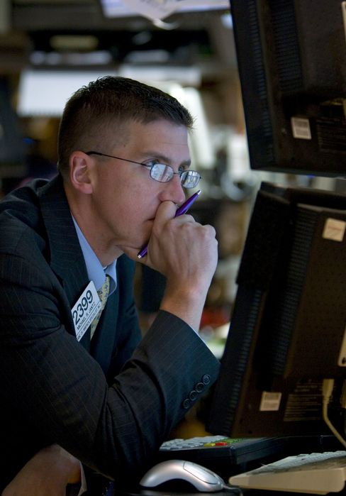 A trader works on the floor of the New York Stock Exchange in New York. Photographer: Jin Lee/Bloomberg