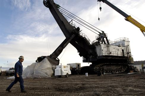 A worker walks past a coal shovel at a mine near Wright, Wyo.