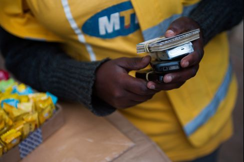 A Vendor Holds Mobile Phones at an MTN Stall