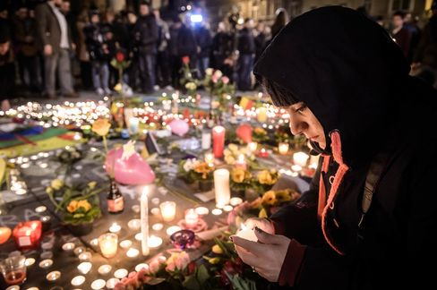 People gather and light candles at the Place de la Bourse