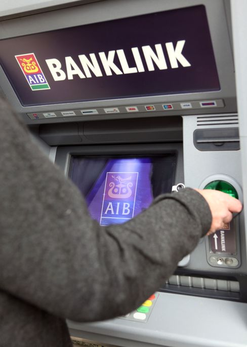 A customer uses an ATM machine at a branch of the Allied Irish Bank. Photographer: Crispin Rodwell/Bloomberg