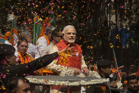 Flower petals are thrown around Bharatiya Janata Party (BJP) prime ministerial candidate Narendra Modi as he rides in an open jeep on his way to file nomination papers on April 9, 2014 in Vadodra, India. Photographer: Kevin Frayer/Getty Images