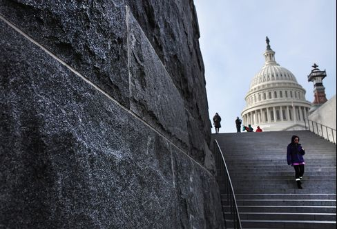 People walk down steps in front of the U.S. Capitol building in Washington. Photographer: David Rogowski/Bloomberg