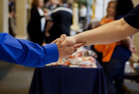 A Job Seeker Shakes Hands with a Representative a Job Fair