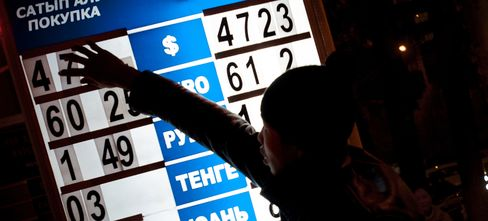 A boy adjusts number tiles displaying the exchange rate on a currency exchange board at night in Bishkek, Kyrgyzstan. Photographer: Noriko Hayashi/Bloomberg