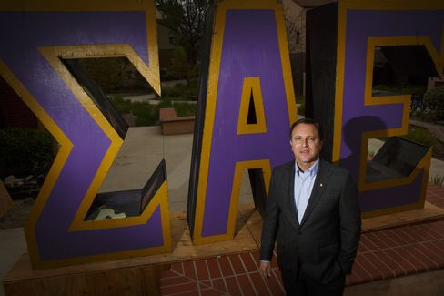 Bradley Cohen, national president of the Sigma Alpha Epsilon fraternity, in front of the Greek letters for the organization, stands outside the chapter house at University of California at Irvine. Earlier this month, Cohen announced an end to pledging, the months-long initiation period when members have been subject to hazing. Photographer: Patrick T. Fallon/Bloomberg