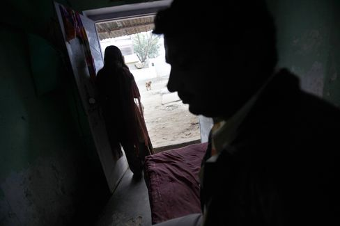 A prostitute stands in her room doorway