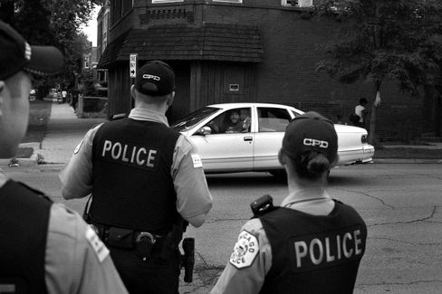 In Chicago's Little Village, authorities are focusing on choke points where they say Sinaloa-supplied drugs change hands from wholesalers to street gangs. Here, a Humboldt Park man tells police he was threatened by a gunman. Photographer: Jon Lowenstein/Bloomberg Markets
