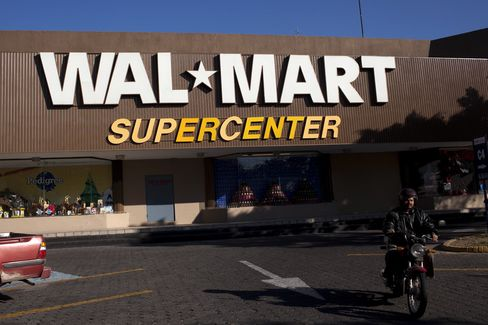 A motorcyclist drives away from a Wal-Mart store in Guadalajara, Mexico. Photographer: David Rochkind/Bloomberg