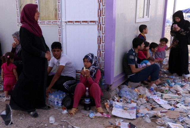 Families gather at a Kurdish checkpoint afterfleeingthe violence in Iraq'snorthern Nineveh province.