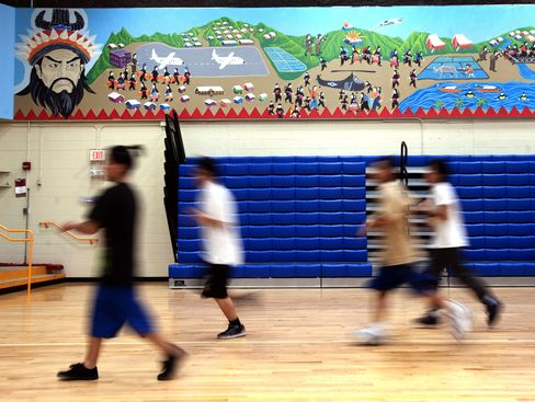 Students run under a mural depicting ancient Hmong leader Chi You and the Hmong flight from Vietnam during gym class at the Hmong College Prep Academy on Dec. 14, 2011 in St Paul, Minn. Photographer: Craig Lassig/Bloomberg