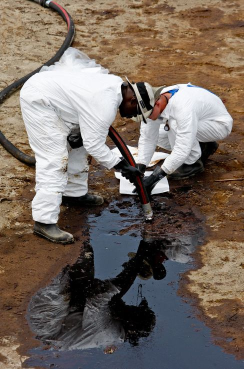 BP Plc contract workers clean up oil
