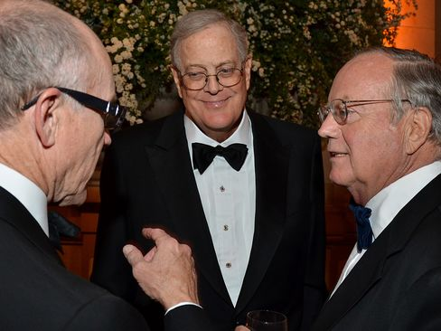 David Koch, executive vice president of chemical technology for Koch Industries Inc., center, speaks with Robert