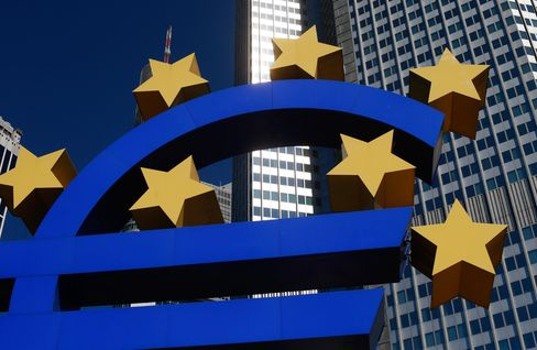 The headquarters of the European Central Bank (ECB) stands beyond a euro sign sculpture in Frankfurt. Photographer: Ralph Orlowski/Bloomberg