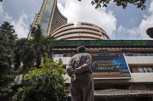 A man looks up at an electronic screen displaying stock figures at the the Bombay Stock Exchange (BSE) in Mumbai on Aug. 19, 2013. Photographer: Prashanth Vishwanathan/Bloomberg