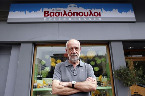 Giorgos Mastorakos poses for a photograph outside the delicatessen he owns in Athens, Greece, on Wednesday, June 18, 2014. Photographer: Kostas Tsironis/Bloomberg