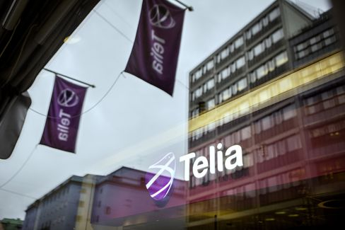 Telia-Branded Flags Seen Through a Window at a Telia Phone Store