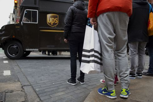 A United Parcel Service Truck Drives Past Shoppers in New York